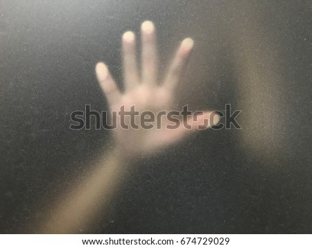 hand behind blur window