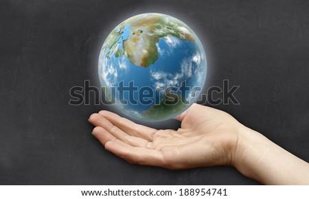 Hand beneath Earth - stock photo
