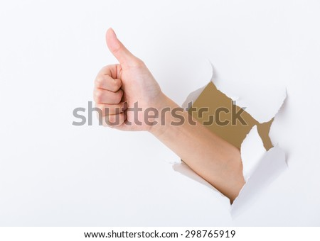 Hand break through paper with thumb up sign - stock photo