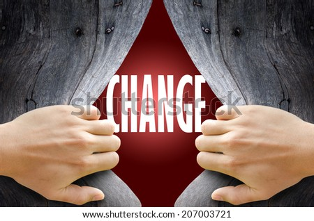 "Hand breaking a wooden wall found the word ""CHANGE"" on the magic red background. - stock photo"
