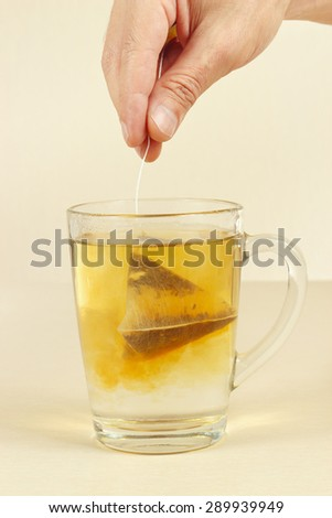 Hand brews tea bag in a cup of boiling water - stock photo