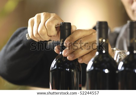 hand broaching bottles of wine - stock photo