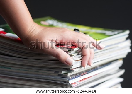 hand browsing through stack of magazines - stock photo