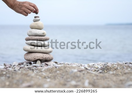 Hand building a pile of smooth stones on the beach  - stock photo