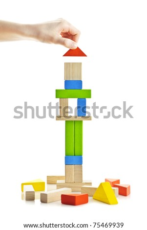 Hand building tower of wooden blocks isolated on white background - stock photo