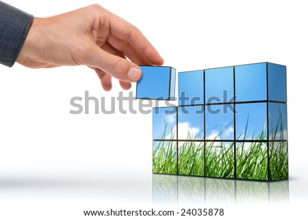 hand building up a grassy panorama against the blue sky - stock photo