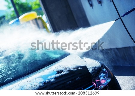 Hand Car Wash Cleaning. Bluish Color Grading. Cleaning Modern Compact Car. - stock photo