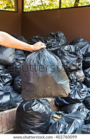 Hand carrying garbage bag over pile of garbage bags in a dump - stock photo