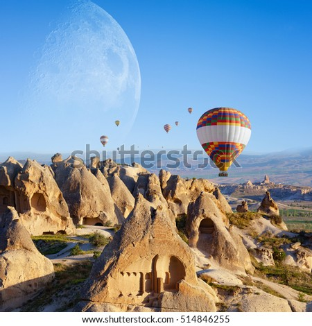 Hand carved rooms in conical rocks near Goreme, Cappadocia, Turkey. Hot air ballooning in sunrise is most popular attraction in Kapadokya. Big moon in clear blue sky.