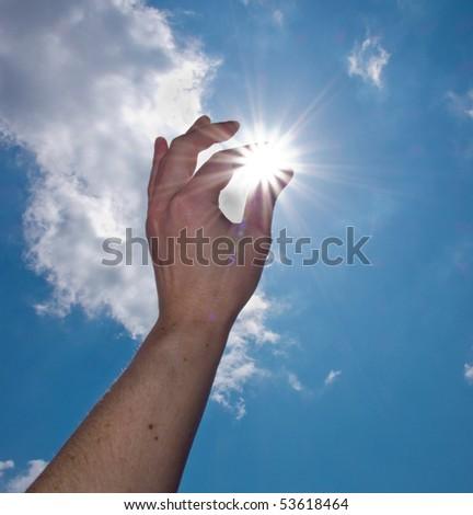 hand catch the sun on blue sky background - stock photo