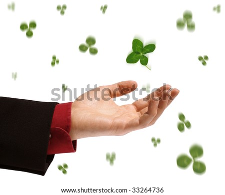 hand catching a clover leaf - stock photo