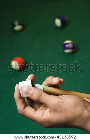 Hand chalking a pool cue with a billiards table in background. Vertical shot. - stock photo