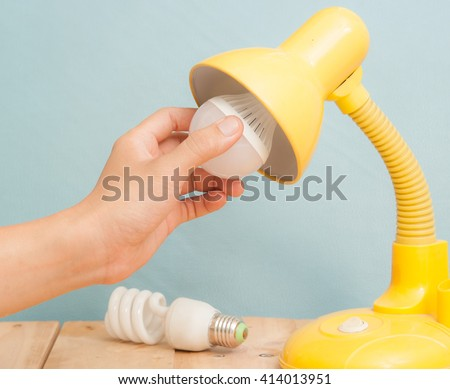 Hand changing a regular light bulb for LED,vintage background