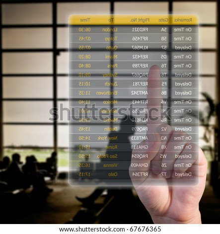 hand choosing flights pushing a screen interface at the airport - stock photo
