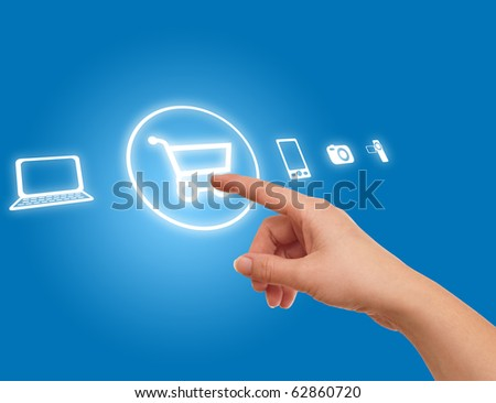 hand choosing shopping cart symbol from media icons on blue - stock photo