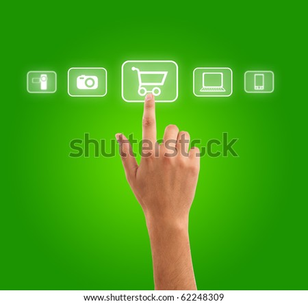 hand choosing shopping cart symbol from media icons on green - stock photo