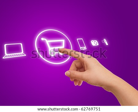 hand choosing shopping cart symbol from media icons on purple - stock photo