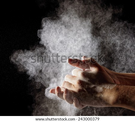 hand clap and white flour on black background - stock photo