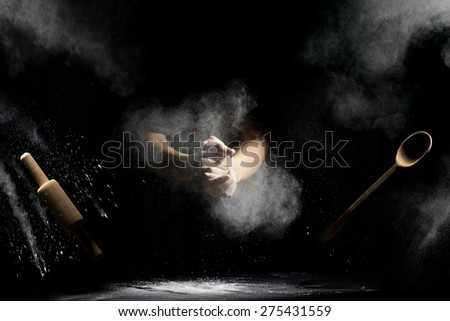 hand clap of chef with wooden rolling pin and spoon in the air with splash flour on black background - stock photo