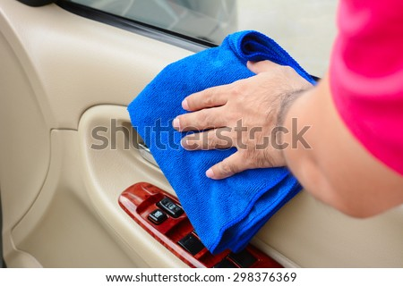Hand cleaning interior car door panel with microfiber cloth - stock photo