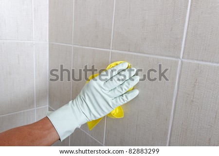 Hand cleaning wall. - stock photo