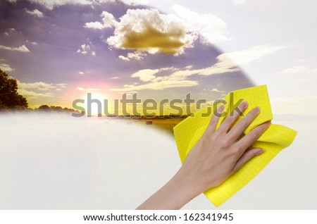 hand cleaning window making it easier to see sunset - stock photo