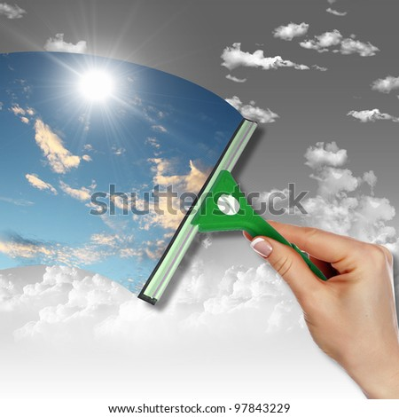 Hand cleaning window with blue sky and white clouds - stock photo
