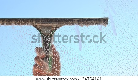 Hand cleaning window with blue sky in the background - stock photo