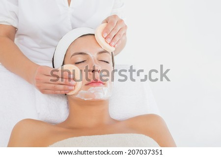 Hand cleaning woman's face with cotton swabs at spa center - stock photo