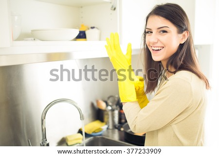 Hand cleaning.Young housewife woman washing dishes in kitchen.Preparing to clean,funny smiling photo with yellow rubber gloves.Smiling young beautiful brunette cleaning kitchen - stock photo