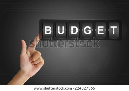 hand clicking financial budget on Flip Board Display - stock photo