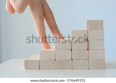 Hand climbing stairs made by wooden blocks  - stock photo