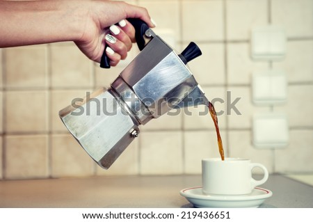 Hand close up pouring espresso coffee in a cup - stock photo