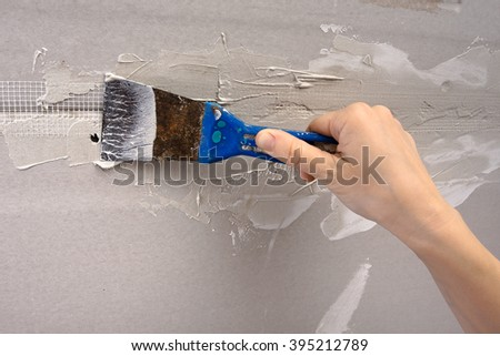hand coating wall of plaster  - stock photo