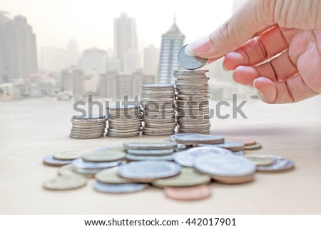 hand collect coins on blur photo de focused city building - stock photo