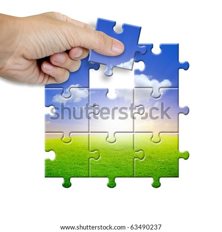 Hand collecting a part of a landscape puzzle - stock photo