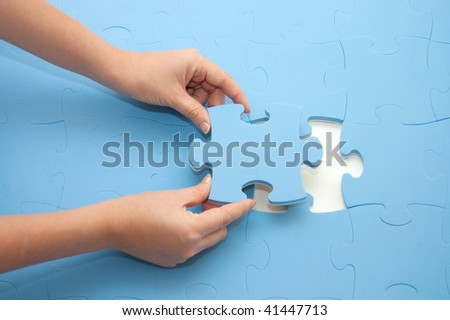 Hand collecting a part of a puzzle - stock photo
