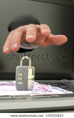 Hand coming out of computer monitor stealing padlock from keyboard. - stock photo