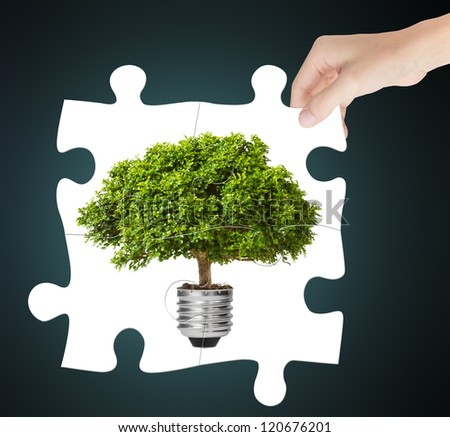 hand completing green energy jigsaw puzzle - stock photo