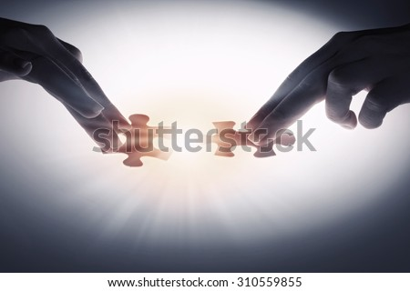 Hand connecting two jigsaw glowing puzzle pieces