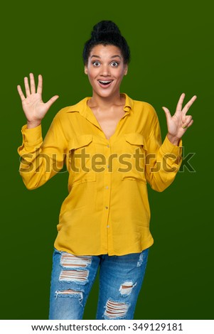 Hand counting - eight fingers. Surprised mixed race african american - caucasian woman indicating the number eight with her fingers - stock photo