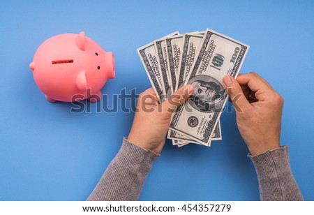 hand counting money and piggy coin saving, blue background, save money concept. - stock photo