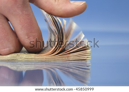 Hand counting money, closeup on blue background with reflections