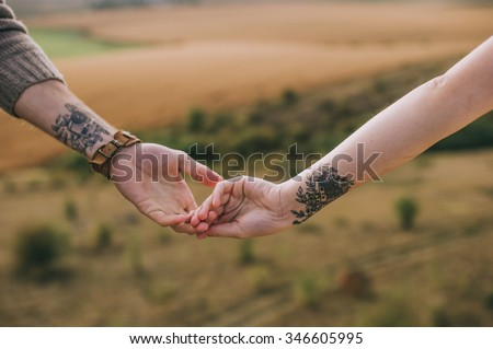 hand couples with identical tattoos - stock photo