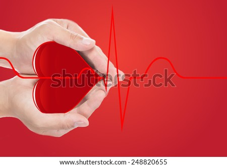 Hand cover red heart and  normal cardiograph on red background  - stock photo