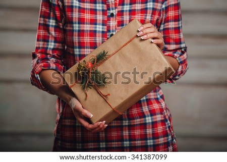 Hand crafted gift box in woman hands, rustic style - stock photo