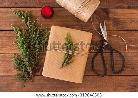 Hand crafted gift on rustic wooden background with Christmas decoration. - stock photo