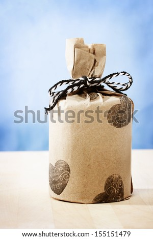 Hand crafted gifts on rustic wooden boards with hearts and ribbon - stock photo