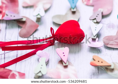 Hand-crafted paper hearts with clothespins on wooden table