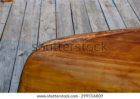 Hand crafted wooden rowboat laying on a deck upside down at dusk - stock photo